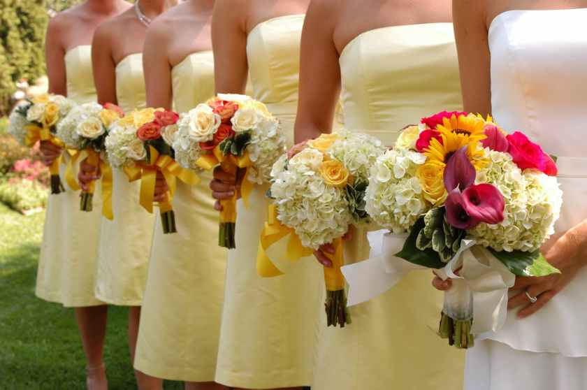 women wears white and yellow tube strapless dresses holding white red and yellow bouquet